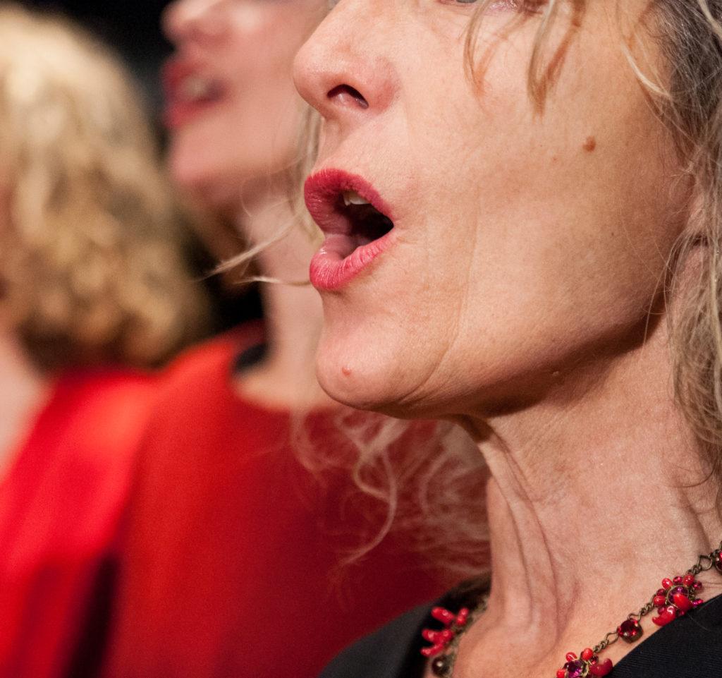 Frau vom Frauenchor bocc'apperta am singen mit geöffnetem Mund